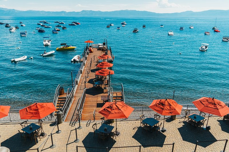 View of bright blue Lake Tahoe dotted with anchored boats with orange umbrellas over dining tables on a deck overlooking the lake