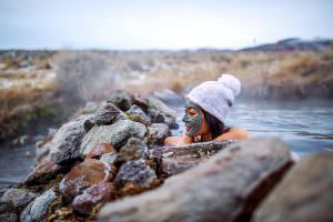 woman soaking in hot spring with mud mask and puff wool hat on